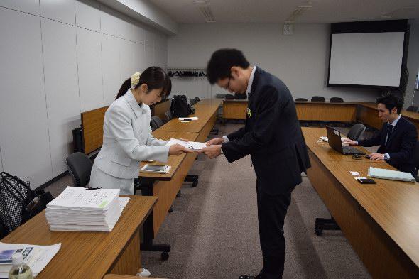 署名を経産省の担当者に提出する東麻衣子さん(左)=4月15日経産省で